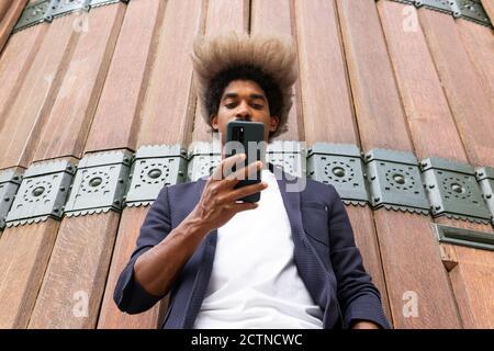 Desde abajo de un hombre africano en traje usando el suyo teléfono móvil frente a una pared de madera