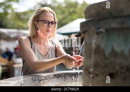 Mujer cucasiana joven y sedienta con mascarilla médica que bebe agua de la fuente de la ciudad pública en un caluroso día de verano. Nueva vida durante el covid