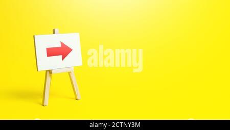 Caballete con una flecha roja a la derecha sobre un fondo amarillo. Señal de dirección. Publicidad de la ubicación de una tienda o un punto de venta. Minimalismo. Restricción de m
