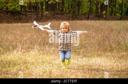Niño feliz jugando al aire libre. Feliz niño jugar avión. Niño pequeño con avión. Un niño sueña con ser piloto. Niño jugando con un avión de juguete Foto de stock