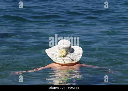 Mujer en sombrero de sol nadando en el mar azul. Relajación en el agua, vacaciones en la playa