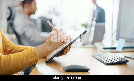 Mujer joven anónima sentada en su escritorio ella está dibujar, escribiendo y usando el lápiz con la computadora de la tableta digital. Céntrese en las manos con Pen. Oficina Bright