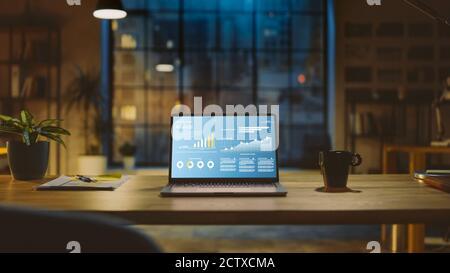 Toma de un ordenador portátil en un escritorio con gráfico de estadísticas, gráfico y varios datos, mostrando el crecimiento y el éxito de la empresa. En el fondo la iluminación cálida de la noche Foto de stock