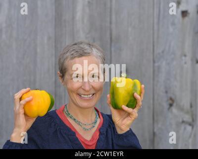 Mujer caucásica canadiense moderna de mediana edad con pelo corto sostiene dos grandes pimientos orgánicos en sus manos.