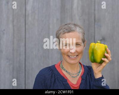 Mujer caucásica canadiense moderna de mediana edad con pelo corto sostiene un gran pimiento orgánico en su mano izquierda.