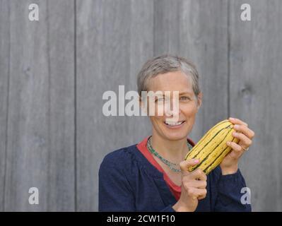 Mujer caucásica canadiense moderna de mediana edad con pelo corto sostiene una calabaza fresca orgánica de boniato en sus manos.