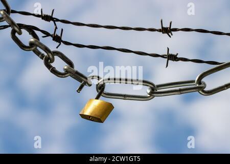 Candado y cadenas de acero con alambre de púas contra azul nublado el cielo simboliza la sujeción