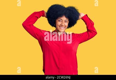 Joven afroamericana con ropa informal relajante y estirada, brazos y manos detrás de la cabeza y el cuello sonriendo feliz