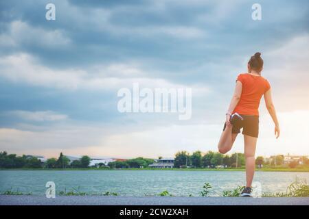 Mujer joven tailandesa de fitness correr estirando las piernas antes de correr parque