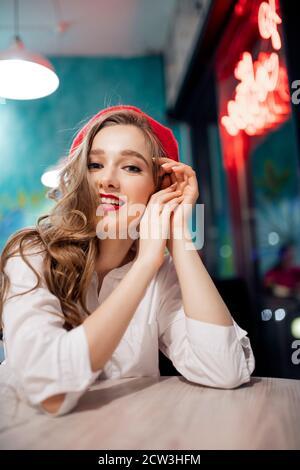 Una joven y bonita mujer francesa en beret rojo está esperando por pedir café y croissant en la cafetería. Concepto de moda retro