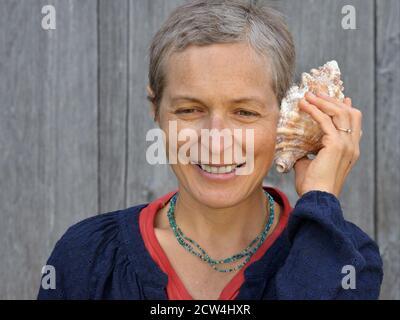 Mujer caucásica canadiense moderna de mediana edad con pelo corto escucha una concha de mar.