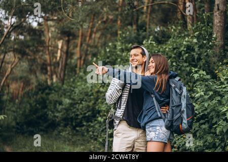 Pareja joven con mochilas en la espalda sonriendo y caminando por el bosque, disfrutar del paseo.