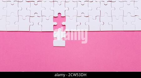 Rompecabezas blanco sobre fondo rosa. Falta la pieza. Vista superior