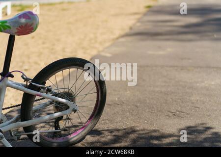 Fotografía de la rueda trasera de una bicicleta infantil aparcada. Ocio tema. Concepto de estilo de vida saludable.