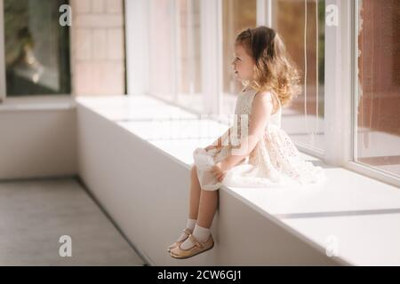 Cute niña de tres años de edad en vestido posando para el fotógrafo en el estudio. Una chica preciosa se sienta en el alféizar de la ventana