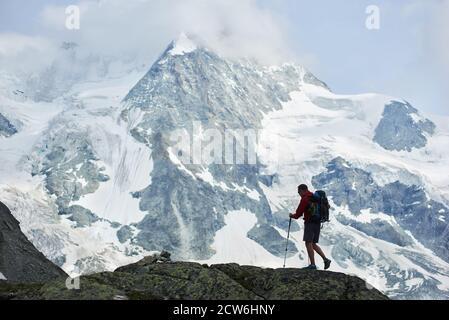Turista masculino con mochila caminando usando bastones de trekking. Increíble, montaña rocosa Ober Gabelhorn en la nieve en los Alpes Peninos en Suiza de fondo. Concepto de turismo, senderismo, alpinismo Foto de stock