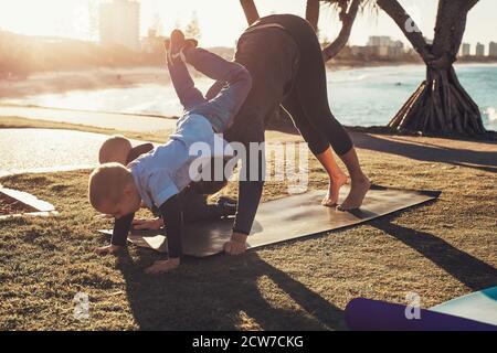 Madre joven y dos hijos haciendo gimnasia y estirándose en el parque de la ciudad al atardecer con vista al océano. Mujer en yoga asana y niño en su espalda