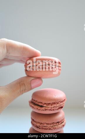 La mano caucásica femenina con esmalte de uñas rosa se muestra tomando un macaron francés rosado de una pila de tres