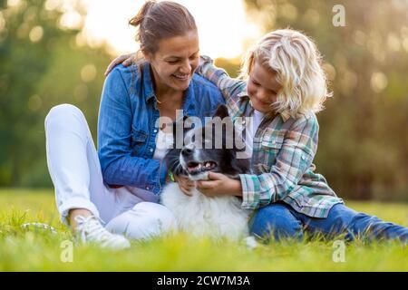 Feliz madre e hijo al aire libre acariciando a su perro