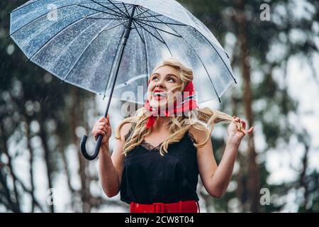 Feliz alfiler de estilo rubio con los labios rojos que caminan adentro día lluvioso al aire libre con paraguas transparente