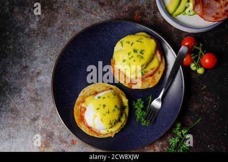 Huevo casero Benedict con huevos escalfados perfecto tocino canadiense coronado con salsa holandesa, enfoque selectivo