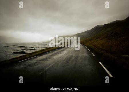 Conducir en clima húmedo una carretera costera islandesa vacía en el paisaje costero de Westfjord en el noroeste de Islandia.