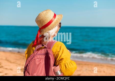Retrato de una joven feliz en un pajizo de verano sombrero y gafas con mochila turística y termo disfrute de la hermosa vista al mar