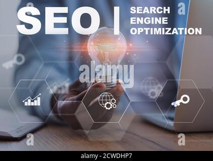 Empresario sosteniendo Lightbulb sentado en la oficina, Seo Collage con texto
