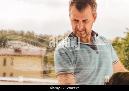Un hombre de mediana edad limpiando la ventana con un trapo y.. un limpiacristales