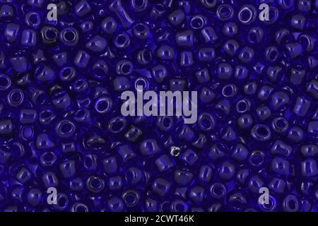 Fondo de abalorios de semillas de vidrio azul, cuentas transparentes sobre el fondo blanco. Fondo o textura de cuentas. De cerca, macro,. Hacer collar de cuentas o str