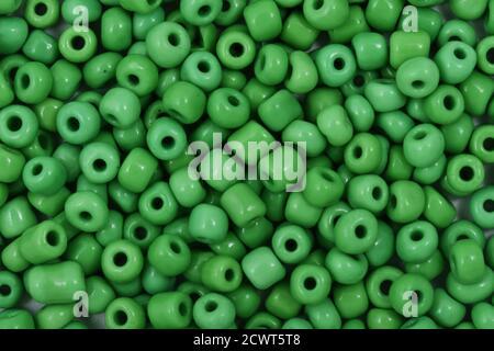 Cuentas verdes sobre el fondo blanco. Fondo o textura de cuentas. De cerca, macro, se utiliza en el acabado de la ropa de moda. Hacer collar de cuentas o St