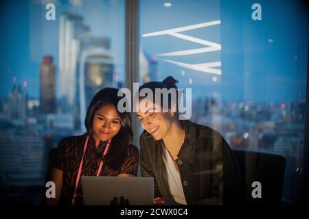 Empresarias con tableta digital trabajando tarde en la oficina, Londres, Reino Unido