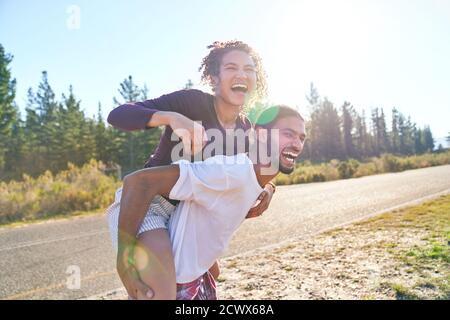 Feliz divertido joven pareja piggybacking en el soleado verano de carretera