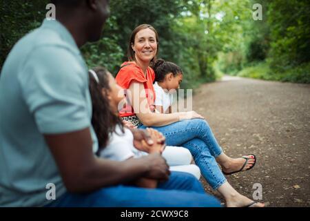 Feliz familia sentada en el banco en el camino en el parque