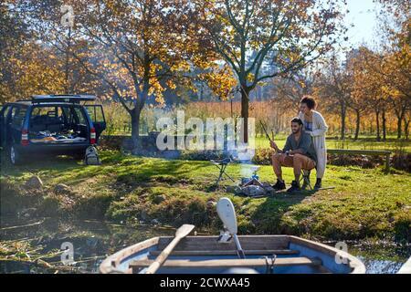 Feliz pareja joven pescando en el soleado otoño a orillas del río