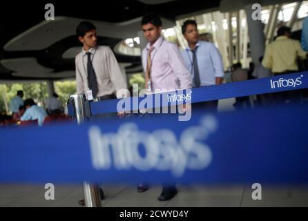 Los empleados de la compañía India de software Infosys caminan por los logotipos de Infosys en su campus en el área de Electronic City en Bangalore el 4 de septiembre de 2012. El subcontratista indio de IT Infosys Ltd, que desde hace mucho tiempo ha dicho que su tamaño de comodidad para las adquisiciones es de hasta el 10 por ciento de sus propios ingresos, está abierto a mayores acuerdos, dada la oportunidad correcta, dijo un alto ejecutivo. REUTERS/Vivek Prakash (INDIA - Etiquetas: TECNOLOGÍA DE LA CIENCIA) Foto de stock