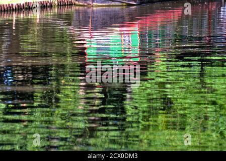 Formas abstractas creadas por los reflejos de estrecha pintada brillantemente barco en el agua