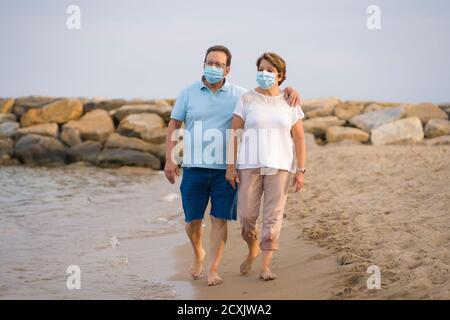 la mujer pensionista y su marido se paseaban juntos por una romántica marcha - feliz pareja adulta jubilada en máscara de cara caminando en el playa en nuevas vacaciones normales t