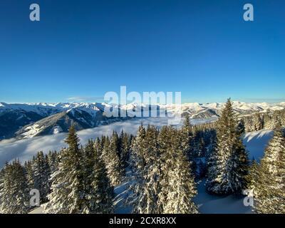 Vista panorámica de las montañas cubiertas de nieve en la región de esquí De Saalbach Hinterglemm en los alpes austríacos bajo una manta de nubes contra el cielo azul en el