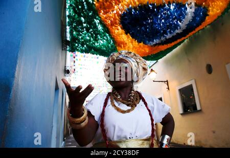 A woman dressed in typical costume of Bahia gestures as she stands on a street of Pelourinho neigborhood ahead of the 2014 World Cup in Salvador, June 11, 2014.   REUTERS/Marcos Brindicci (BRAZIL - Tags: SPORT SOCCER WORLD CUP SOCIETY TPX IMAGES OF THE DAY)