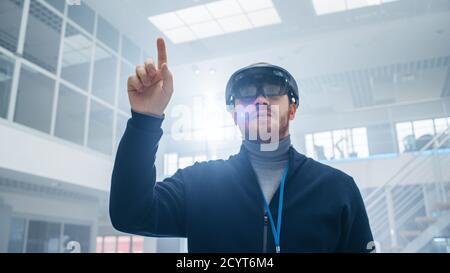 Ingeniero de automoción con auriculares de realidad aumentada y piezas virtuales móviles en el aire. En Innovación instalación de Laboratorio de Alta Tecnología con futurista