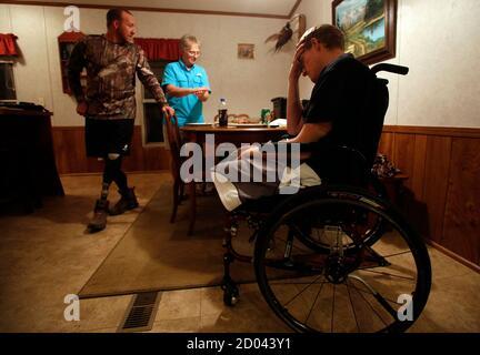 SGT. Matt Krumwiede del Ejército de los Estados Unidos (R) se sienta en dolor mientras su amigo Sgt. Jesse McCart y su madre Pam Krumwiede hablan, después de un día de caza en un rancho en las afueras de San Antonio, Texas, en este archivo de fotos del 2 de noviembre de 2013. Krumwiede estaba patrullando en Afganistán en 2012 cuando pisó un improvisado artefacto explosivo que desgarró ambas piernas, dañó el brazo izquierdo y abrió su cavidad abdominal. Desde entonces ha sufrido docenas de cirugías y ha pasado tiempo recuperándose en Brooke Medical Center en San Antonio, Texas, aprendiendo a caminar de nuevo con el uso de prótesis de piernas. En junio de 201
