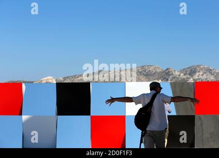 A visitor gestures as he walks past a creation as part of the exhibition 'Defini Fini Infini, Travaux in situ'  by French artist Daniel Buren at the MaMo art center in Marseille September 12, 2014. The MaMo contemporary art center is installed on the restored rooftop terrace of Le Corbusier's 1947 Cite Radieuse (Radiant City) and created by French designer Ora-Ito. The exhibition will run until September 30, 2014.           REUTERS/Jean-Paul Pelissier (FRANCE  - Tags: ENTERTAINMENT SOCIETY)