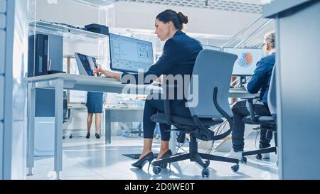 Vista posterior del equipo de ingenieros tecnológicos que trabajan en equipos de escritorio en Bright Office. Las pantallas muestran el software IDE / CAD, implementación de la máquina