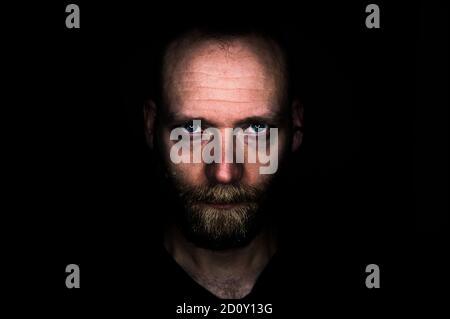 Un hombre mira seriamente en la cámara desde la oscuridad. Su mirada es amenazadora y decidida.