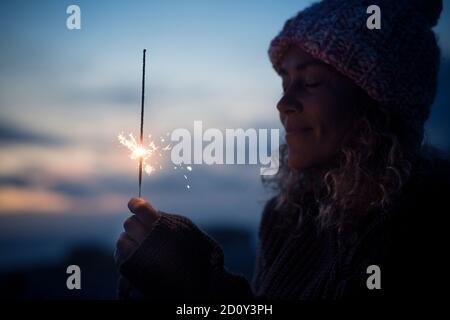 Celebración y esperanza concepto futuro con hermosa mujer retrato con disparó a sparkler en la oscuridad de la noche alrededor - fin de año y celebración i
