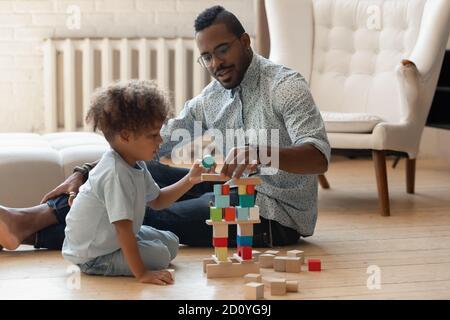 Afectuoso y cariñoso papá afroamericano jugando con su hijo.