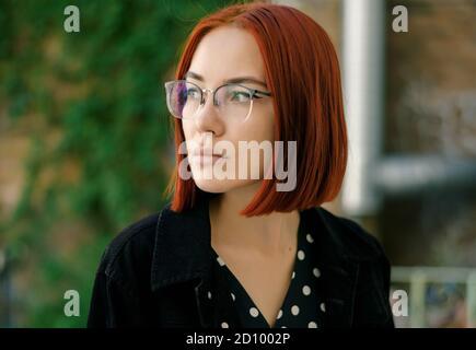 Retrato de una hermosa mujer de la pelirroja usando gafas.