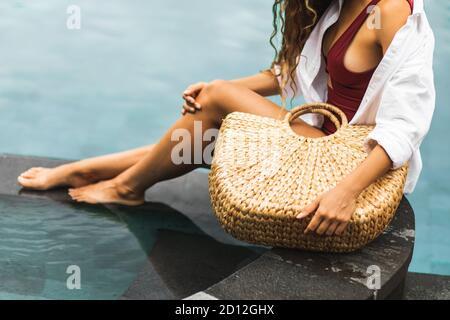 Mujer cerca de la piscina sosteniendo en manos mano paja mimbre bolsa de playa. Estilo de vida tropical ecológico y sin residuos. Orgánico y natural, sin plástico.