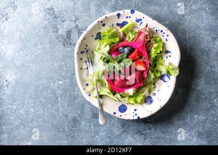 Ensalada de frutas veganas con bayas, ensalada verde y menta servida en fruta de dragón rosa en placa de cerámica manchada sobre fondo de textura azul. Vista superior, copiar